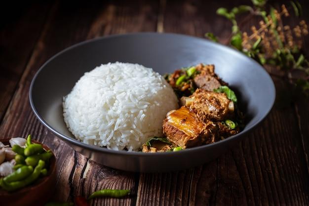Thais eten, rijst gegarneerd met roergebakken basilicum en varkensbot.