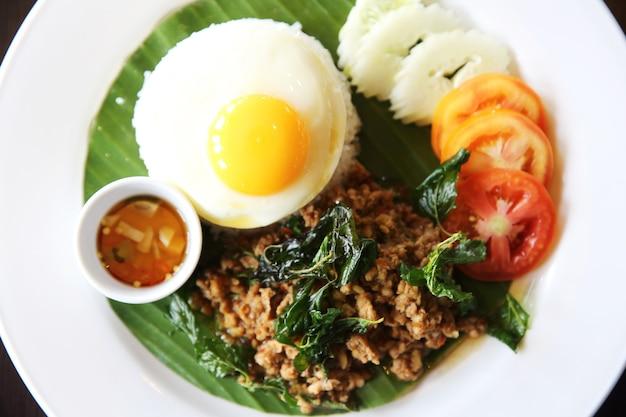 Thais eten rijst gegarneerd met roergebakken varkensvlees en basilicum