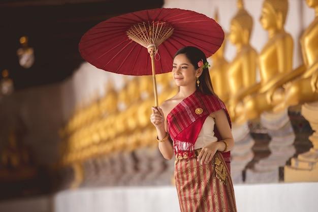 Thais meisje in traditioneel thais kostuum met rode paraplu in thaise tempel, identiteitscultuur van thailand.