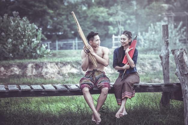 Thais paar dat op traditionele kleren met paraplu's op een houten brug zit