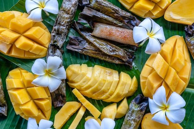 Thais stijldessert, gele mango met plakkerige bananenrijst in palmbladeren. gele mango en plakkerige rijst is een populair traditioneel dessert van thailand. detailopname