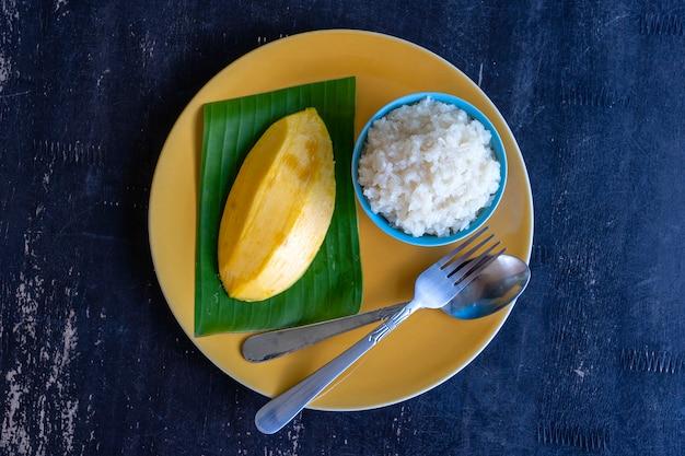 Thais stijldessert, mango met kleefrijst op plaat.