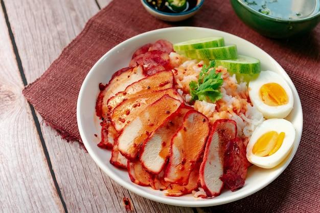 Thais straatvoedsel - geroosterd rood varkensvlees met gekookte eieren en met rijst bedekte zoete saus