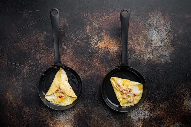 Thaise aziatische omelet, verse rode chili, bruin en wit krabvlees, citroen, cheddar kaas en eieren, op koekenpan, op oude donkere rustieke achtergrond, bovenaanzicht plat leggen