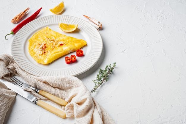 Thaise aziatische omelet, verse rode chili, bruin en wit krabvlees, citroen, cheddar kaas en eieren, op plaat, op witte achtergrond, met copyspace en ruimte voor tekst