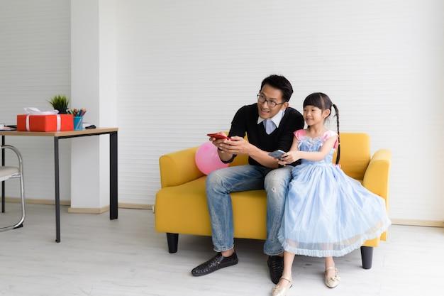 Thaise aziatische vader en dochter zitten op de bank en spelen spelletjes op de mobiele telefoon die is aangesloten op het externe scherm, leuk en gelukkig in de woonkamer thuis.