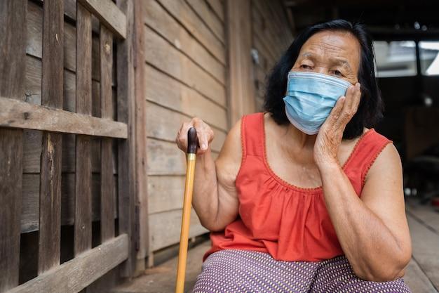 Thaise bejaarde vrouw in mouwloze kraag met ronde hals die medisch masker draagt ter bescherming van coronavirus (covid-19) pandemie in oud houten huis