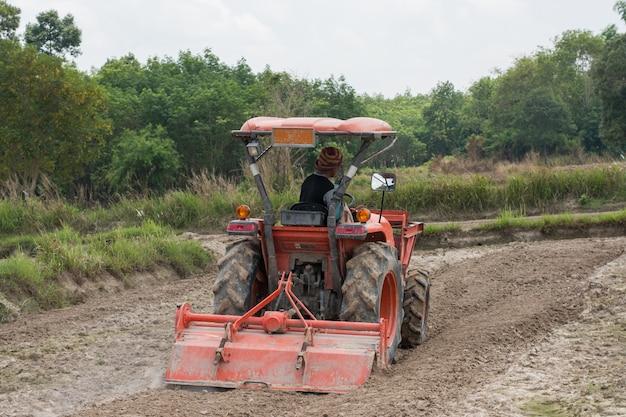 Thaise boeren gebruiken een tractor om de grond klaar te maken voor het telen van rijst.