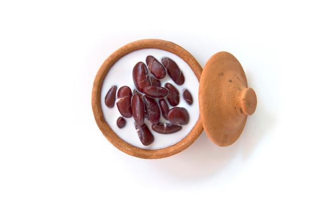 Thaise die dessert rode boon in kokosmelk met kleipot op witte achtergrond wordt geïsoleerd