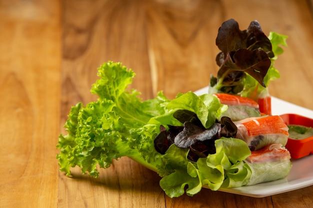 Thaise die saladebroodjes met kruidige garlicky-onderdompeling op een houten vloer wordt geplaatst.