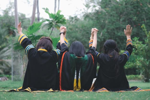Thaise groepsvrouwen die afstudeerjurken dragen en vanaf de achterkant in het park zitten.