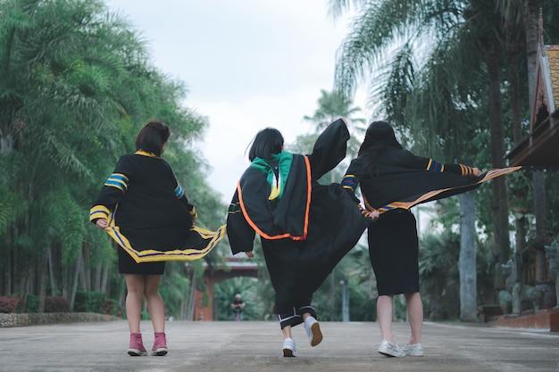 Thaise groepsvrouwen die afstudeerjurken dragen en vrolijk vanaf de achterkant in het park springen.