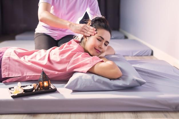 Thaise hoofdmassage op bed met kaars en plumeria-bloem in kuuroordsalon