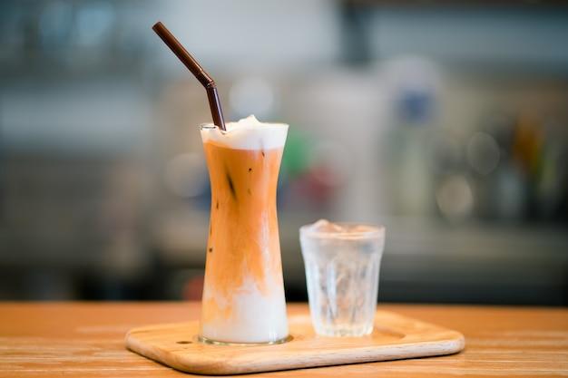 Thaise ijsmelkthee geserveerd met een glas water
