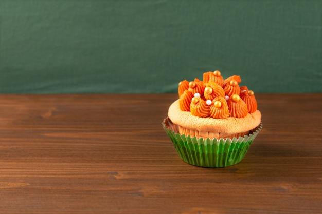 Thaise ijsthee cupcake op houten raad en groene achtergrond met exemplaarruimte