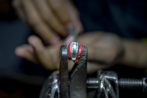Thaise juwelier, behandelt de sieraden en edelstenen in de werkplaats, het proces van het maken van sieraden, close-up
