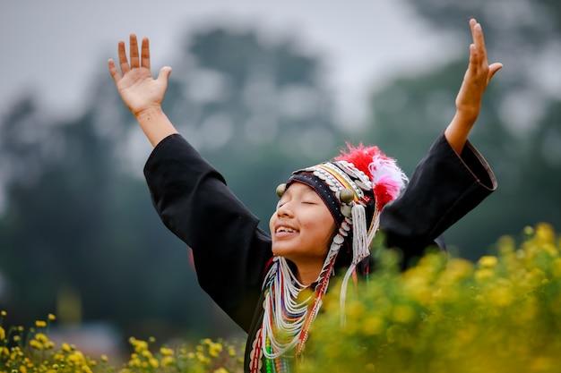 Thaise karen-bergvrouwen heffen hun wapens op op het gebied van chrysantenbloemplanten
