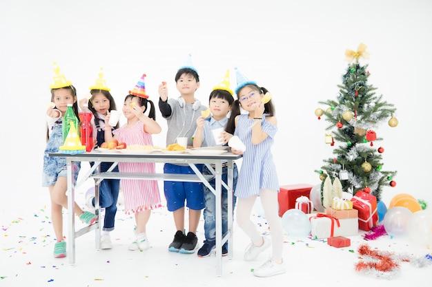 Thaise kinderen uit chang asia dragen traditionele kleding en mooie hoeden. ze dragen snacks op tafel vol met verschillende zoetigheden in een witte kamer gevuld met ballonnen, geschenkdozen en een kerstboom