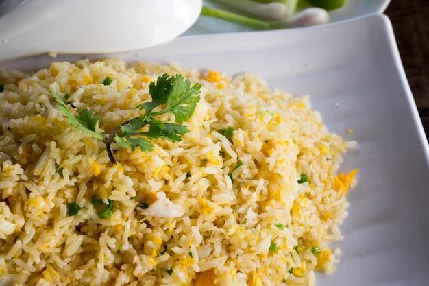 Thaise krab gebraden rijst op witte schotel met komkommers