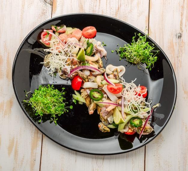 Thaise kruidige en zure zeevruchtensalade op een houten lijst