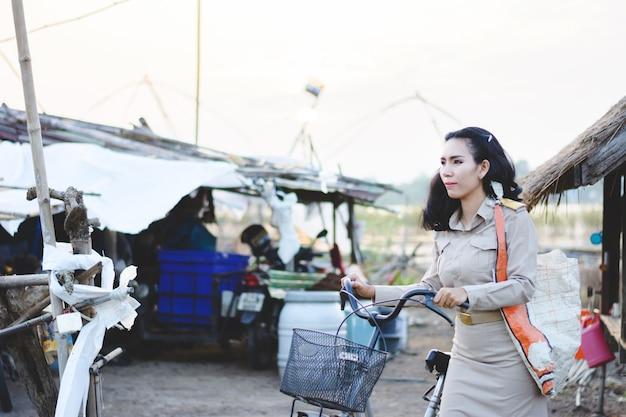 Thaise landelijke leraar berijdende fiets openlucht, portret van aziatische vrouw in thaise leraar eenvormig op gebied,