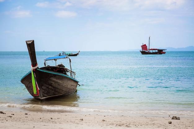 Thaise longtailboot op strand van phra nang, afgemeerd op de zandachtergrond van een zwart zeilschip