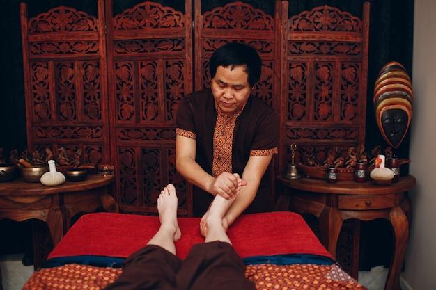 Thaise man die klassieke benen thaise massageprocedure maakt aan jonge vrouw bij beauty spa salon