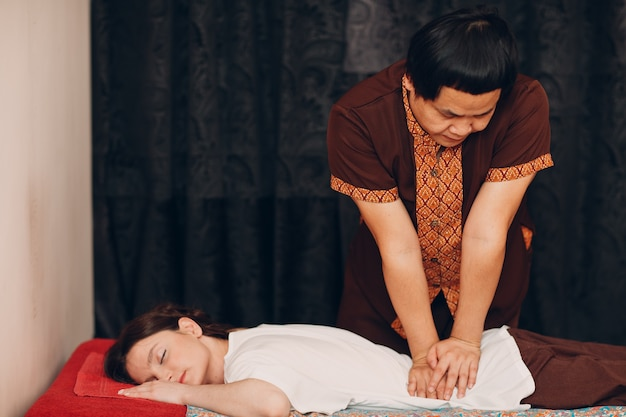 Thaise man die klassieke thaise massageprocedure maakt met jonge vrouw bij beauty spa salon