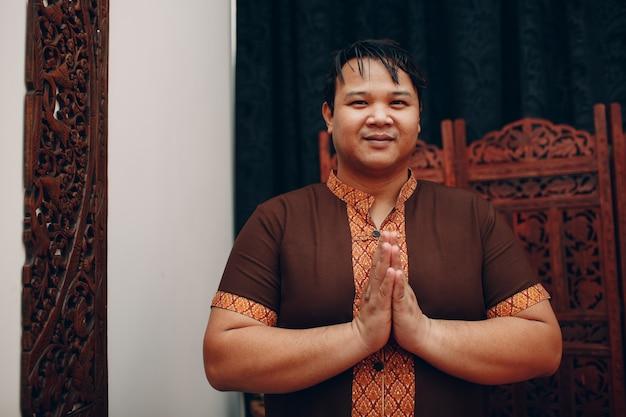 Thaise man glimlachend portret met traditionele thaise pak en welkom bidden gebaar gevouwen handen