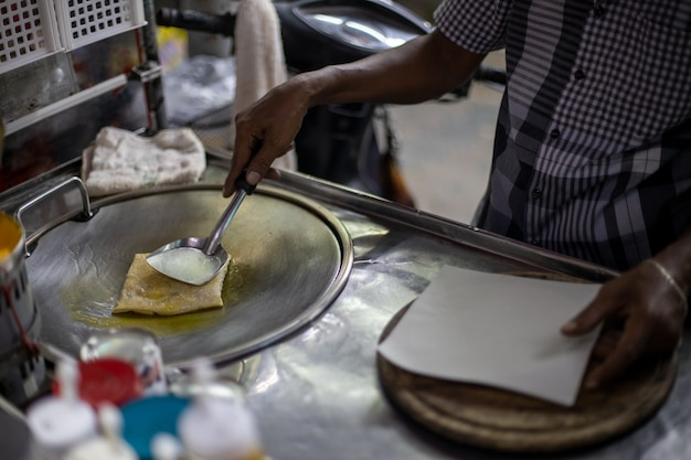 Thaise man koken en verkopen van traditionele thaise zoete pannenkoeken op straat. detailopname