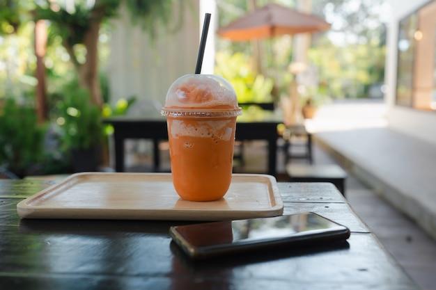Thaise melkthee frappe in afhaalbeker geserveerd met houten dienblad in de buurt van mobiele telefoon op zwarte houten tafel