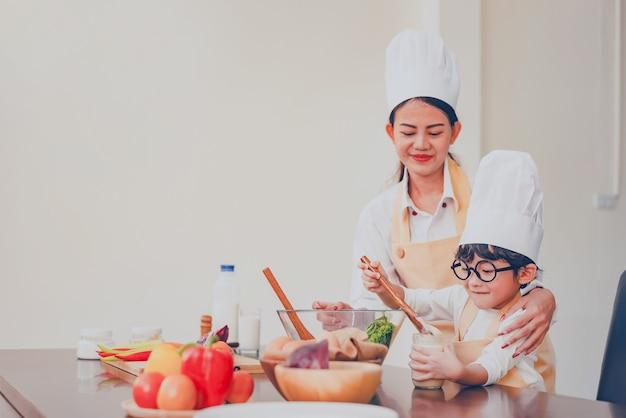 Thaise moeder en kind koken samen thuis. social distancing en blijf thuis blijf veilig. gezinsactiviteit effect van covid-19 en stop uitbraakvirus. opsluiten en thuis in quarantaine.