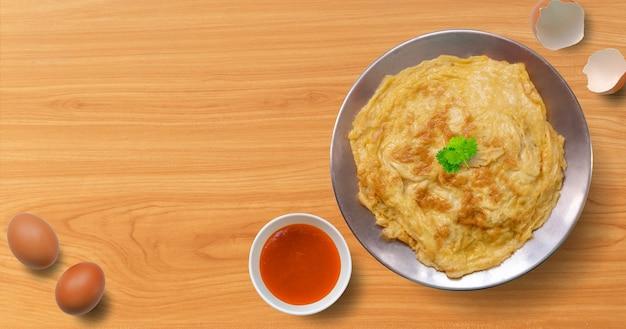 Thaise omelet met chilisaus op houten tafel