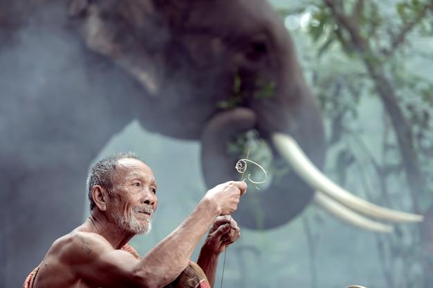 Thaise oude man die bamboe slijpt en gelukkig rookt terwijl hij een olifant grootbrengt
