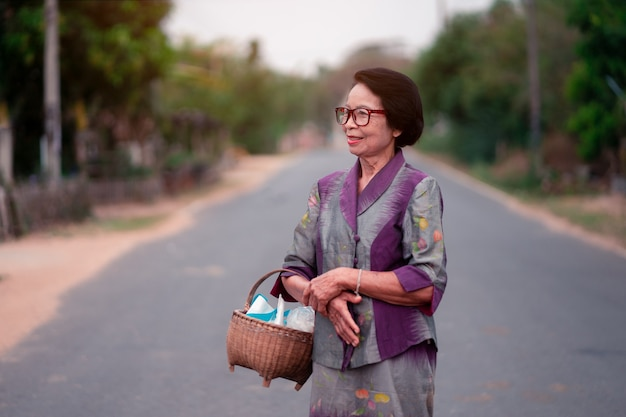 Thaise oude vrouwen die bamboemand op platteland van thailand houden