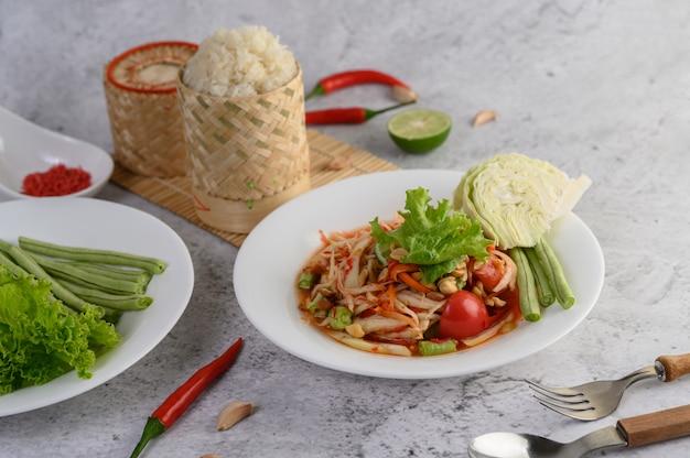 Thaise papajasalade in een witte plaat met kleefrijst en gedroogde garnalen