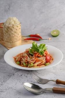 Thaise papajasalade in een witte plaat met kleverige rijst