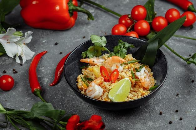 Thaise rijst met garnalen in een zwarte plaat op een donkere achtergrond. copyright plaats