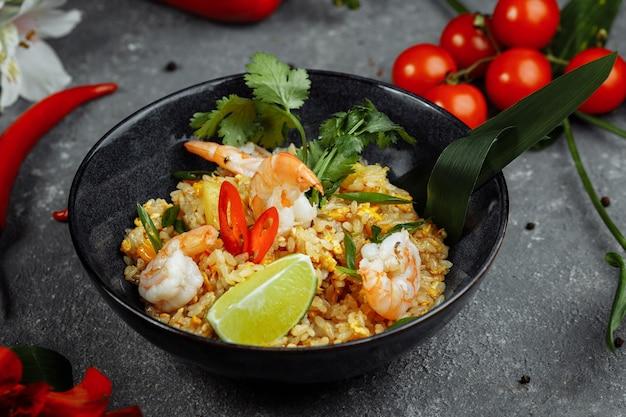 Thaise rijst met garnalen in een zwarte plaat op een donkere achtergrond
