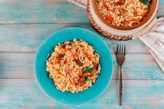 Thaise rijst met vlees en groente op blauw bord.