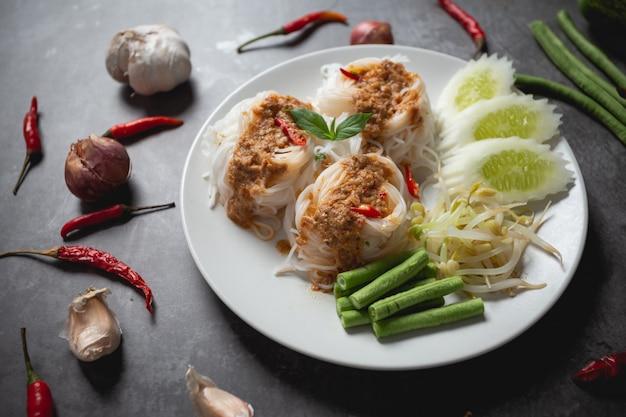 Thaise rijstnoedels in de saus van de vissenkerrie op houten lijst.