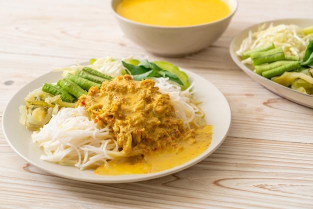 Thaise rijstnoedels met krabcurry en verschillende groenten - thais lokaal zuiders eten