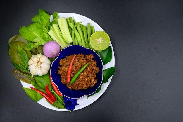 Thaise stijl chilisaus met veel groenten op zwarte achtergrond, plat leggen