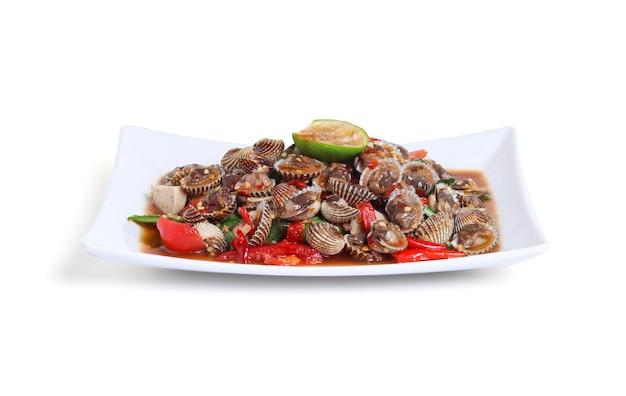 Thaise stijl pittige zeevruchtensalade met kokkel geïsoleerd op een witte achtergrond, uitknippad, kokkelsalade heet en pittig schaaldieren bloed kokkels salade mix groente tomaat kruid en specerijen thaise stijl eten