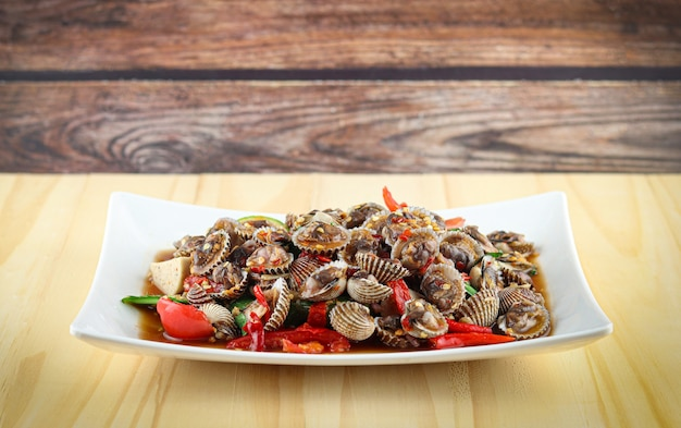 Thaise stijl pittige zeevruchtensalade met kokkel op houten achtergrond, kokkelsalade hete en pittige schaaldieren bloed kokkels salade mix plantaardige tomaten kruid en kruiden thaise stijl eten.