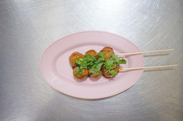 Thaise varkensvleesballetjes met bruine zoete saus op plastic schotel.