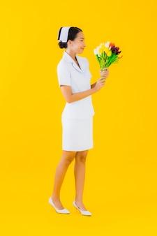 Thaise verpleegster van de portret de mooie jonge aziatische vrouw met bloem