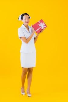 Thaise verpleegster van de portret de mooie jonge aziatische vrouw met rode giftdoos