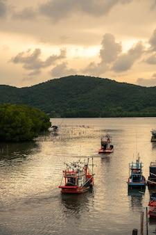 Thaise vissersboten varen 's avonds bij zonsondergang de zee op.