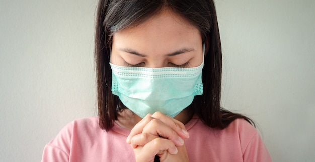 Thaise vrouw die een masker draagt om het virus te beschermen, covid 19 bidden om zegeningen van god zodat de wereld veilig is voor deze epidemie.